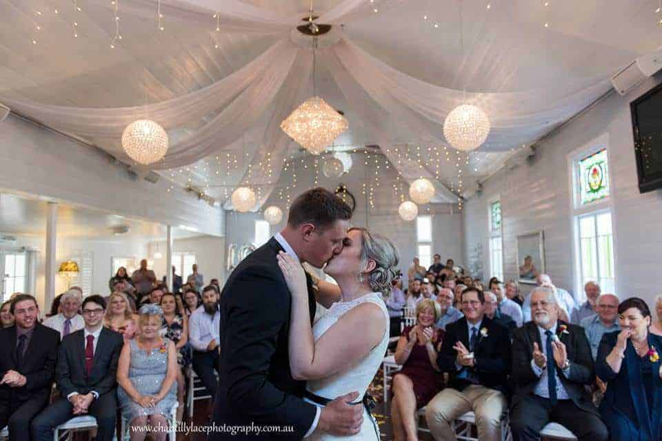 A young couple getting married with guests seated in the chapel our our ipswich and brisbane wedding venue